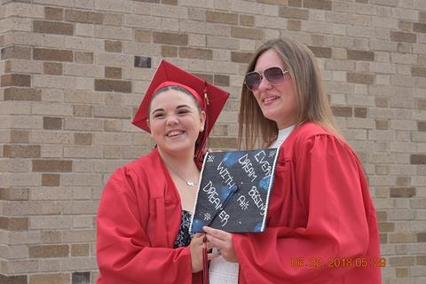 Two female grads pose with decorated caps
