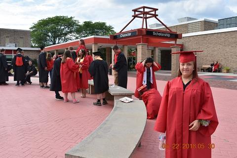 Candid photo of grads in front of school; one female grad is prominent at right front, looking at camera