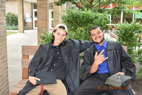 Two male graduates wearing black gowns unbuttoned, smiling