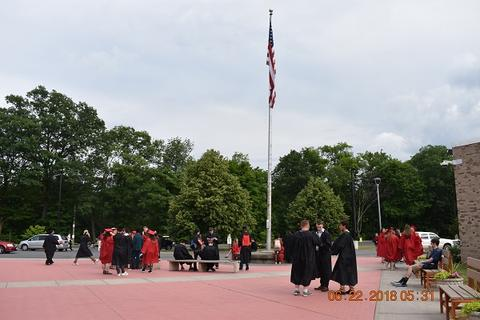 Candid distance shot of grads near flagpole