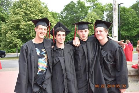 Four male grads with arms around each other, smiling for camera