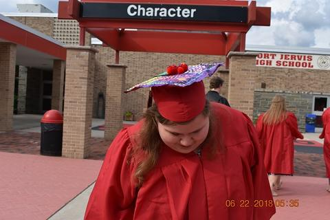 Female grad leans down to show red pompoms on grad cap