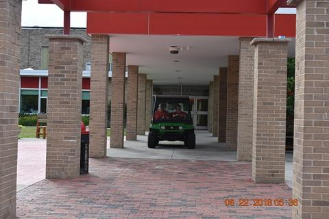 People driving a tractor under awning of high school entrance