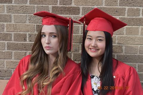 Two female grads with caps; one smiling, one not