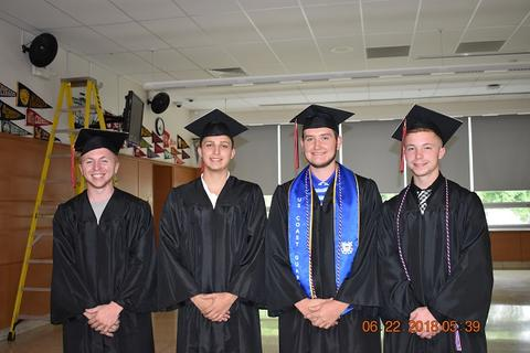 Four male grads in black gowns and caps, smiling