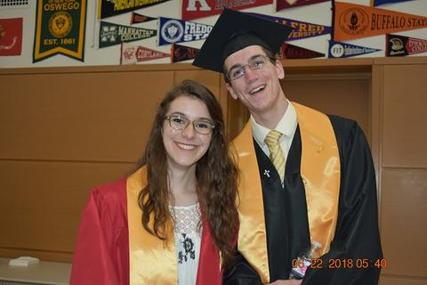 Male and female grad with yellow sashes