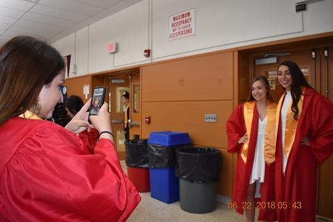 Grad taking photo of two female graduates