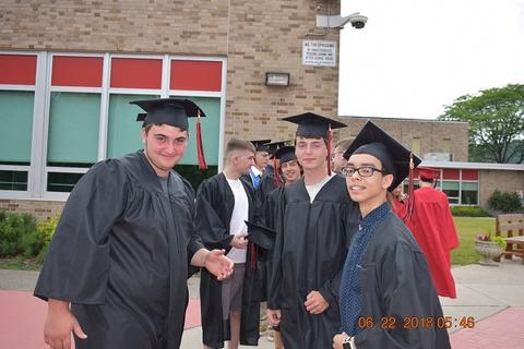 Three male grads smile for camera outside