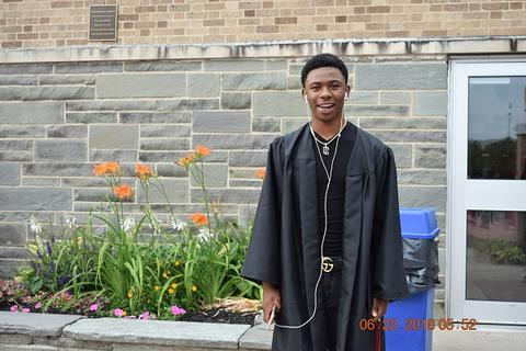Male grad poses with open gown and ear buds