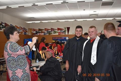 Parent takes picture of three male grads
