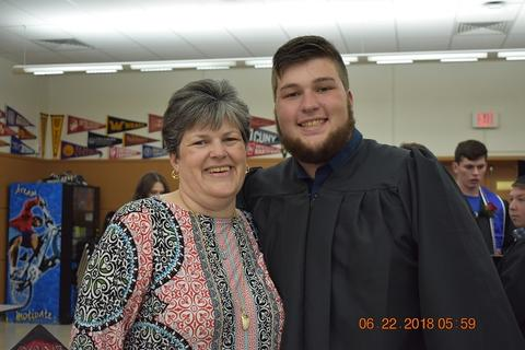 Mom and son graduate pose and smile for camera
