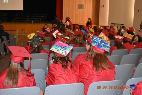 From behind, graduates at ceremony; many have decorated caps