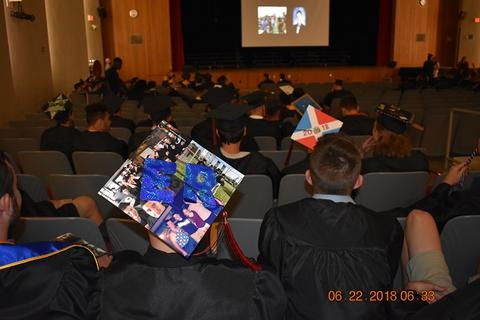 From behind, male graduate's decorated cap says E.R.