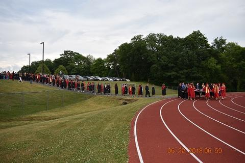 Long shot of long line of grads and processional walking toward track