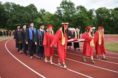 Graduates with flag at front of processional walking on track