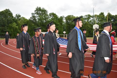 Male grads holding flag at front of graduation processional