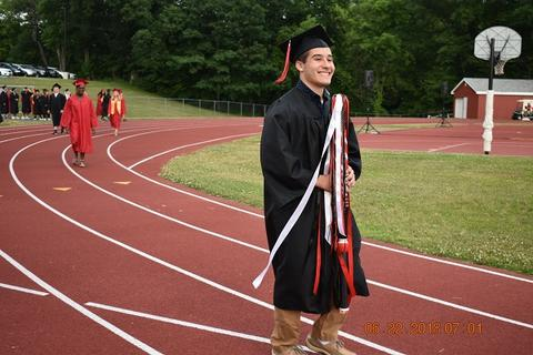 Male grad with academic sashes on track