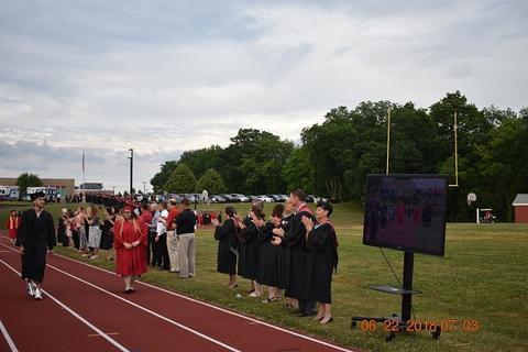 Spectators clap as grads walk the track