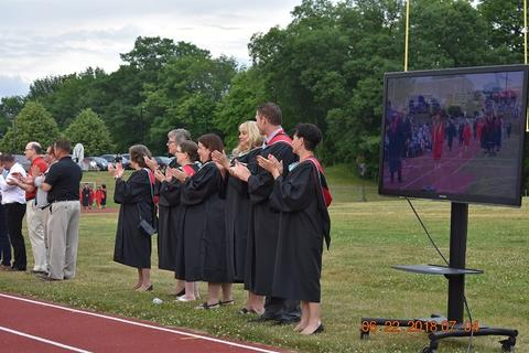 Baccalaureate staff clap track-side