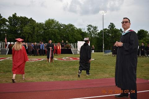 Female and male grad walk toward midfield as black gown clad staff member looks at camera