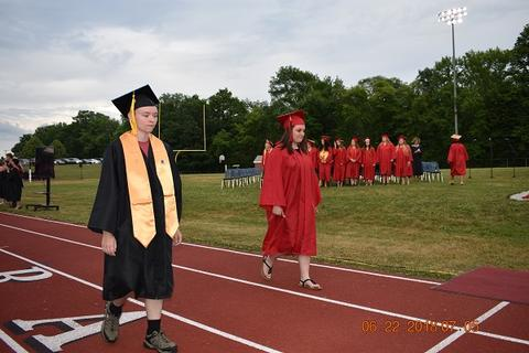 Male grad with honors walks next to female grad on track