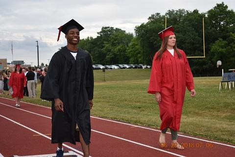 Smiling male grad walks next to female grad on track