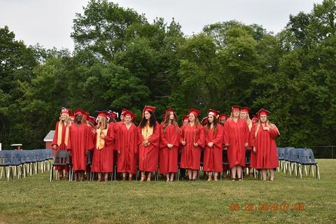 All female graduates stand in a group in front of chairs