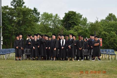 All male graduates stand as a group in front of chairs