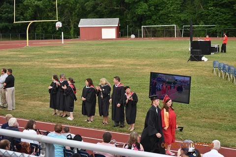 Shot from the bleachers, view of processional and TV with grad images