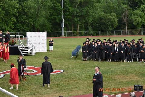 Staging midfield, with grads in black gowns and a white panel screen