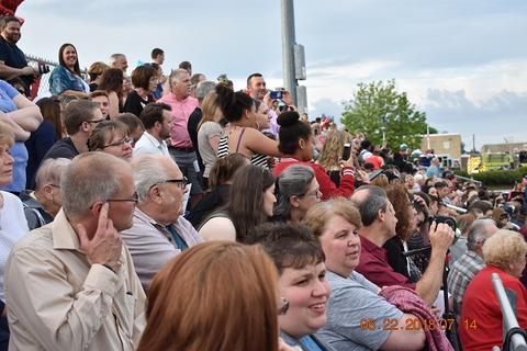 Lots of people in bleachers watching graduation
