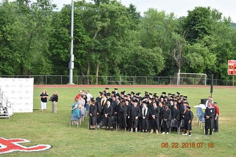 Long-distance shot shows male graduates seated on their side of the field