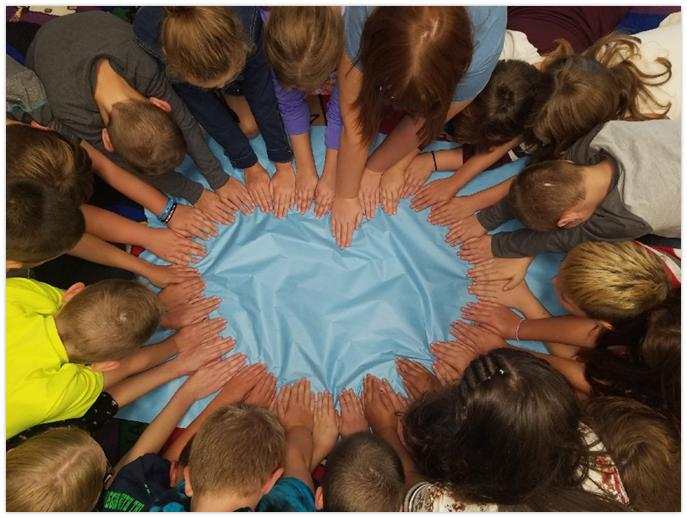 HBE students form a heart shape by placing their hands in the middle of the ring.