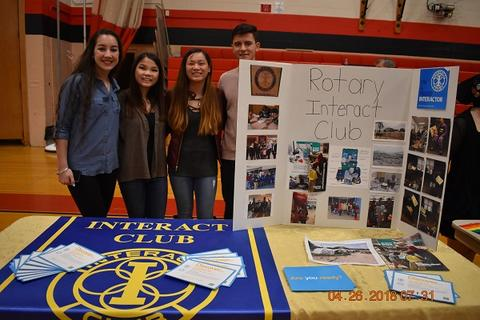 Four students stand behind Rotary International table display