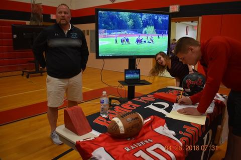 Coach stands behind Football table, with sports jerseys and a TV showing sports