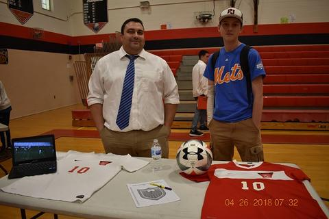 Coach and student stand behind soccer table, with jerseys and a soccer ball