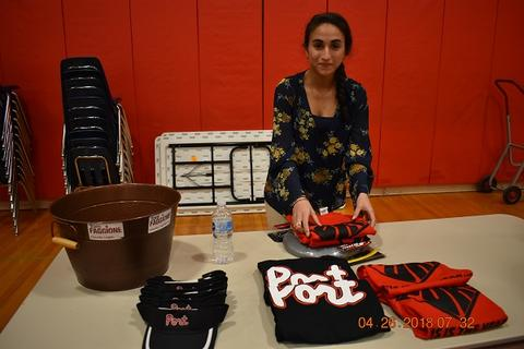 Female student stands behind a table with school pride merchandise; hats and shirts