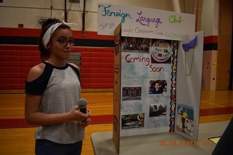 Student holding a microphone stands next to the Foreign Language Club table display