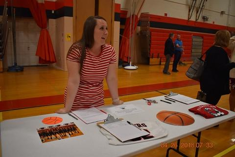 Coach stands behind table for girls' basketball