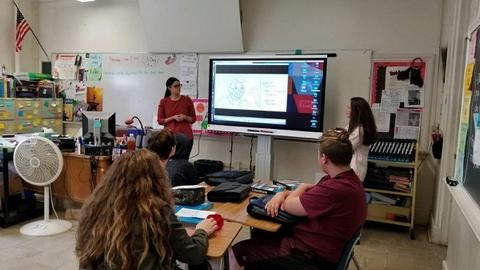 Adult female shows students onscreen presentation at front of class