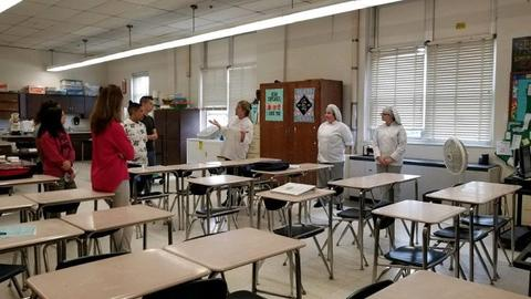 Three women in white food service uniforms talk to several students