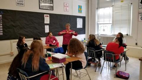 Woman with glasses and red shirt is pulling something between her fingers while speaking with students