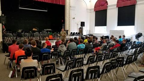 Person in military fatigues speaking with students in auditorium