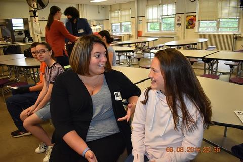 Woman with bob haircut and black jacket speaking with young student, who is smiling enthusiastically