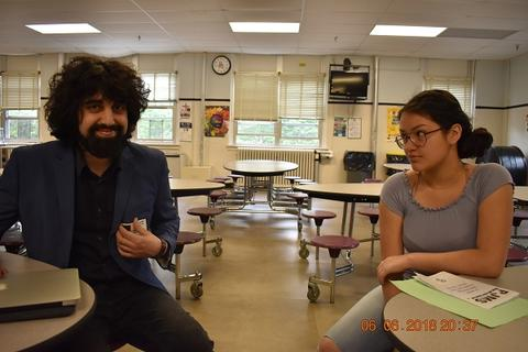 Adult with suit, bushy beard and hair, sitting next to a student who is giving him a suspicious look