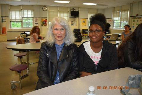 Woman with white hair and black jacket sitting next to student with glasses and black sweater