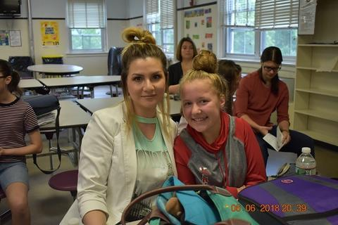 Woman with blond ponytail and white jacket sits next to blond student