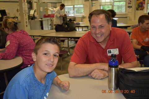 Male student in blue t-shirt sits next to adult male in red polo shirt; both are smiling.