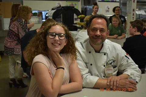 Smiling student with long hair and glasses sits next to adult male in chef's outfit