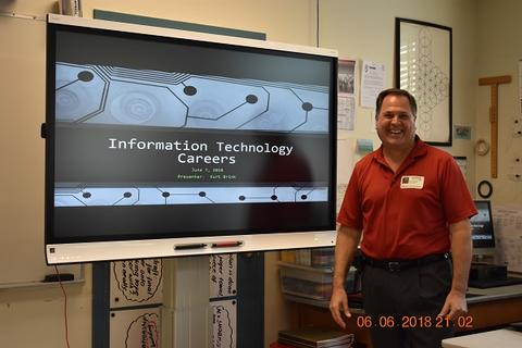 Man in red polo shirt stands next to presentation on Information Technology careers